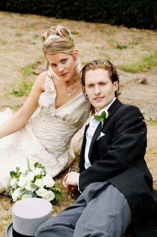 Bride and Groom have a rest on the grass during a Richmond wedding reception.