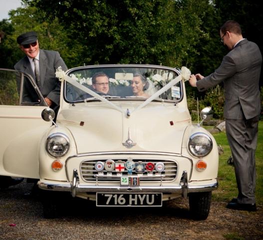 Vintage Morris Minor departs Kent wedding with the Bride and Groom